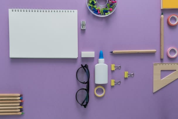 Top view over a pink background with school supplies on it. Back to school concept. Office supplies in a cartoon style.