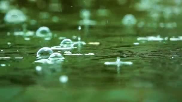 Kapky deště padající na zpomalený pohyb vody