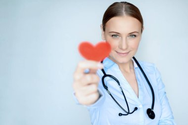 Portrait of a woman doctor with red heart in hand isolated on blue background, cardiology center, photo with copy space, health care concept