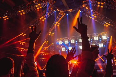 Rock concert, people with raised up hands dancing and enjoying loud music, having fun in night club, with pleasure spending time on musicl festiva