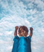 A fiú játszik a superman, hátsó kilátás nyílik egy kis fiú visel szuperhős jelmezben emelte fel kezét próbál repülni az égen, boldog gyermekkor fogalma
