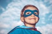 Vértes portré egy szép kis szuperhős át kék ég háttér, egy vidám gyermek visel maszkot superman és cape, boldog gyermekkor fogalma
