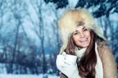 Gyönyörű boldog mosolygós nő csésze kávé felett áll gyönyörű téli park háttér, visel meleg kalap és egy forró ital, élvezi a téli vakáció