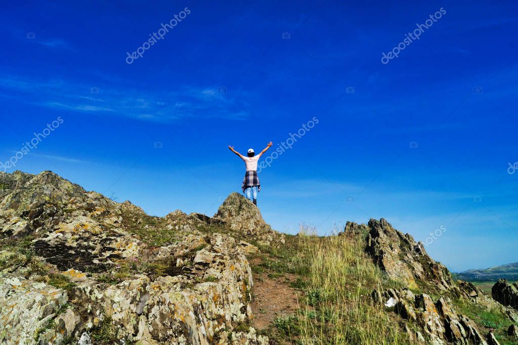 Picture with a victorious person on sharp crests under blue sky