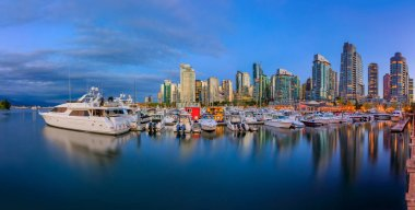 August 04, 2018 - Vancouver, Canada: Sunset panorama at Coal Harbour with downtown buildings, boats and reflections in the water
