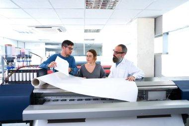 Printing team at industry plotter printer men and woman