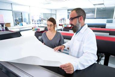 Printing team at industry plotter printer man and woman