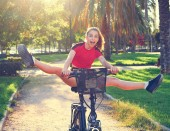 Akrobatisches Mädchen auf E-Bike im Stadtpark mit rotem T-Shirt faltbarem E-Bike