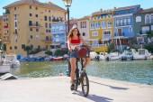 Fotografie Mädchen mit dem faltbare e-Fahrrad in einem mediterranen Yachthafen Port ebike