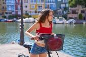 Mädchen mit faltbarem E-Bike in einem Mittelmeerhafen