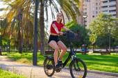 Fotografie Mädchen mit rotem T-Shirt und faltbarem E-Bike im Stadtpark