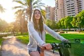Brünettes Mädchen fährt Fahrrad im Park mit Kapuzenpullover