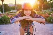 Fotografie Mädchenporträt auf Fahrrad mit Helm lächelt glücklich im Blumenpark im Freien
