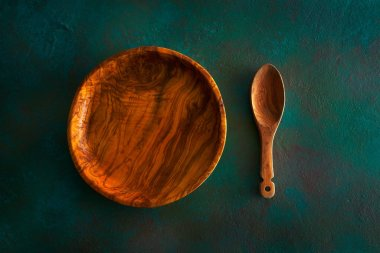 Wooden tableware on grungy green background