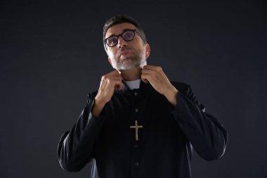 """Картина, постер, плакат, фотообои """"священник натягивает шейного священника на черное """", артикул 222030516"""