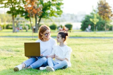 Funny mom and daughter with modern laptop outdoors