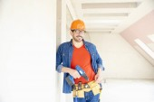 Portrét mladého opravář nosit přilbu a nástroj pás a pomocí kladiva Vrtací šroubovák při práci na staveništi