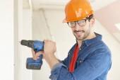 Fotografie Detailní portrét mladý opravář nosit přilbu a nástroj pás a pomocí kladiva Vrtací šroubovák při práci na staveništi