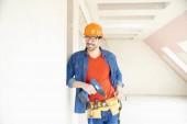 Fotografie Portrét mladého opravář nosit přilbu a nástroj pás a pomocí kladiva Vrtací šroubovák při práci na staveništi