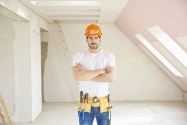 Handsome young handyman wearing hard hat and tool belt while standing at construction site.