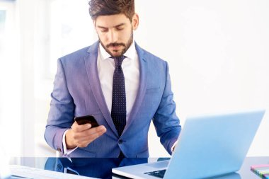 Executive financial advisor businessman wearing suit and using his cell phone while sitting at office desk and working on an investment project.