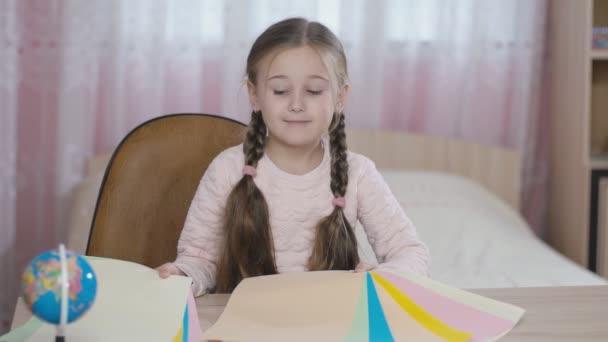 little girl throws sheets of paper