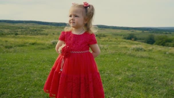 malá holčička v červených šatech