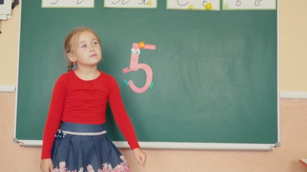 the girl is standing near the blackboard