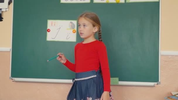 dívka stojící vedle tabule