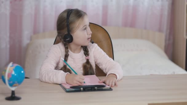 little girl with headphones sitting at table