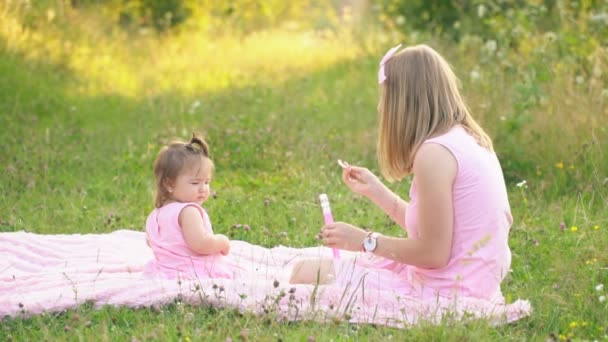 mom and daughter are sitting on the lawn