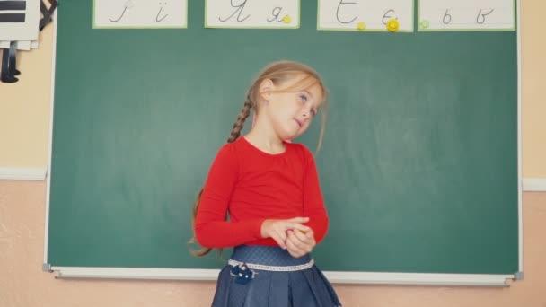 das Mädchen steht neben der Tafel