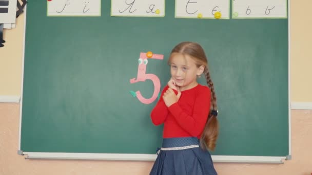 the girl is standing near the blackboard