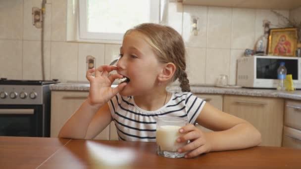 malá holka pije jogurt v kuchyni
