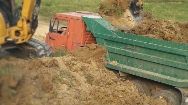 Bagger belädt einen Lastwagen