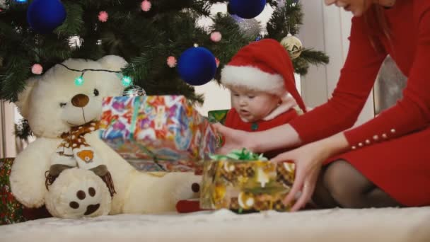 mom with baby in santa costume looking at presents