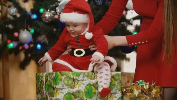 Mutter mit Baby im Weihnachtsmannkostüm schaut sich Geschenke unter dem Weihnachtsbaum an