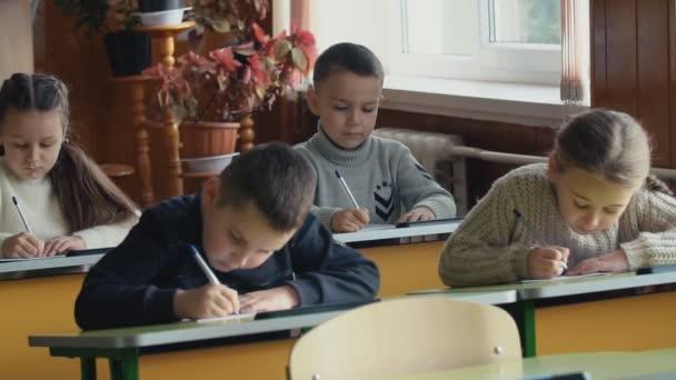 Gyermekek írni ül az asztalon