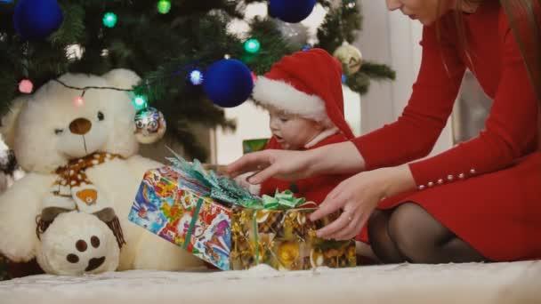 Mutter mit Baby im Weihnachtsmannkostüm schaut sich Geschenke an