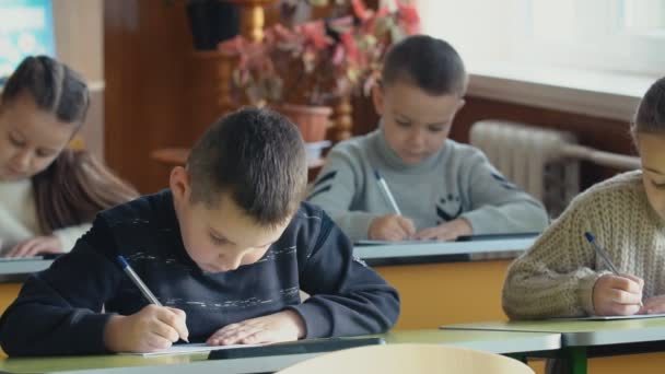 Children write while sitting at the school desk