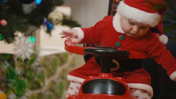Ein kleines Mädchen im Weihnachtsmannanzug rollt mit einem Spielzeugauto in der Nähe eines Neujahrsbaums