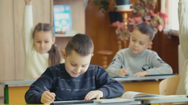 Children write sitting at a desk