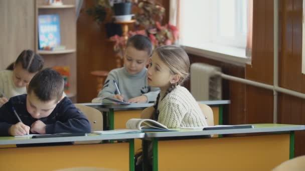 Children write sitting at a desk
