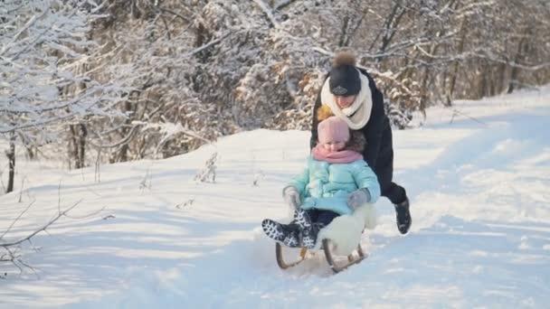Mutter rollt ihre Tochter auf einem Schlitten