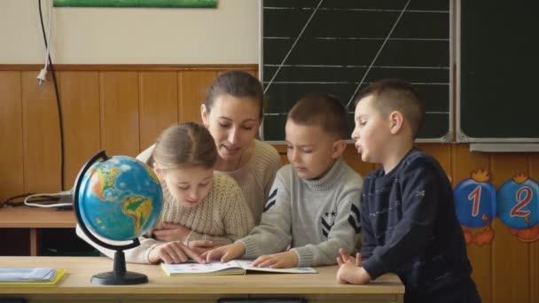 Lehrer mit Kindern betrachten ein Buch