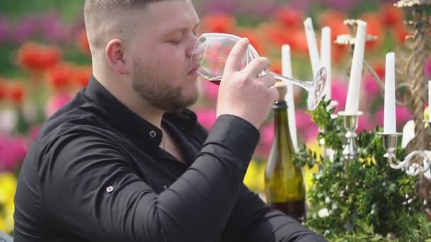 man drinking wine sitting at the table