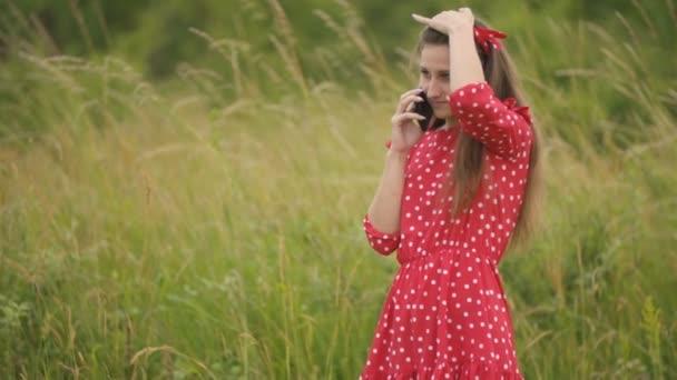 dívka v červených šatech na telefonu