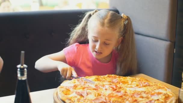malá holčička krájí pizzu