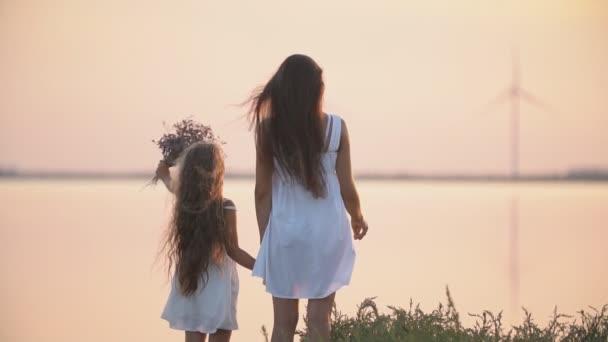 Mutter und Tochter stehen am Meeresufer