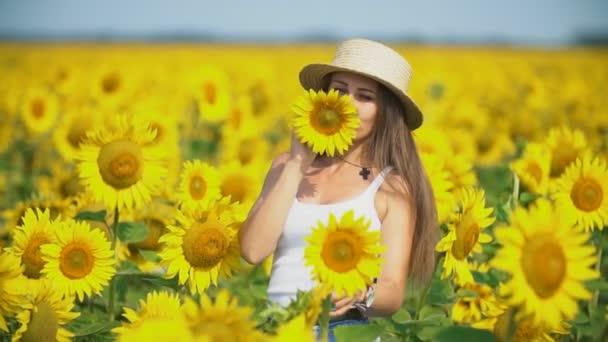 dívka v klobouku na pozadí slunečnicových květů